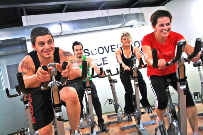 Happy people sweating in spin cycling class