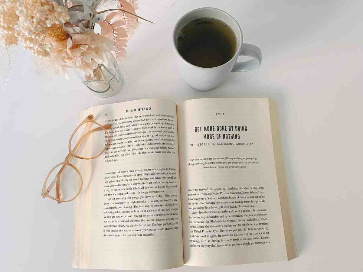 flowers, tea, glasses and happiness book to inspire you to challenge the happiness misconceptions