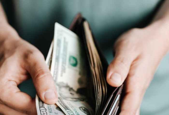 crop man getting dollars from wallet