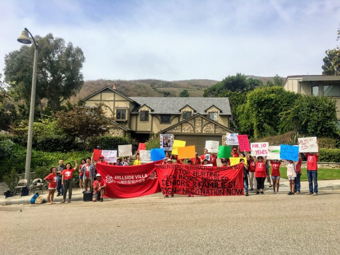 People displaying colorful signs stand in front of a mansion