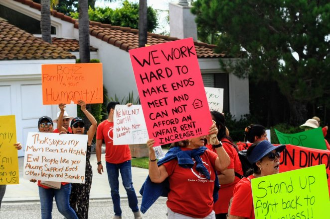 """A protester holds a sign reading """"WE WORK HARD TO MAKE ENDS MEET AND CAN NOT AFFORD A RENT INCREASE"""" while surrounded by others also displaying signs of their own"""