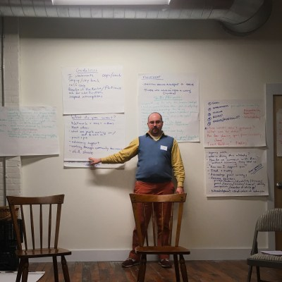 Trainer Toby Davis standing in front of chart paper on a white wall.