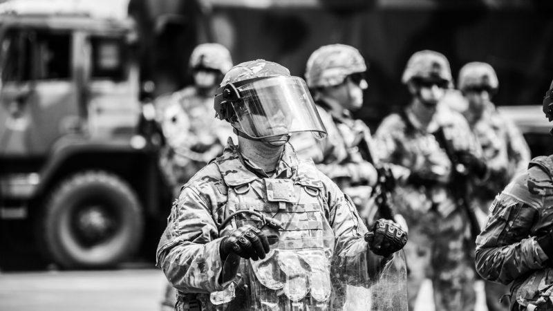 grayscale photo of man in helmet and helmet