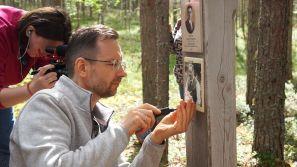 Максим Лялин устанавливает памятную табличку в Сандармохе. Фото Н. Деминой