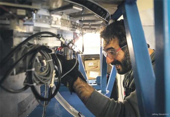 Аспирант Джонатан Кауфман пополняет запас жидкого гелия, необходимого для нормальной работы датчиков BICEP2, регистрирующих космический микроволновый фон. Фото Jeffrey Donenfeld с сайта http://ucsdnews.ucsd.edu