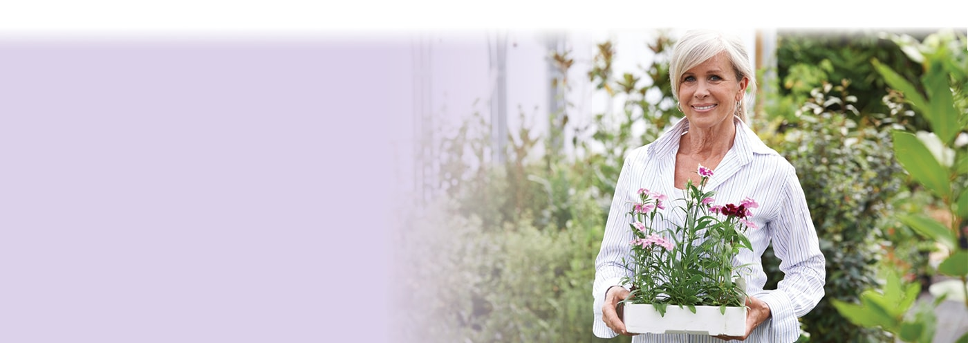 Older woman holding potted flowers in greenhouse garden