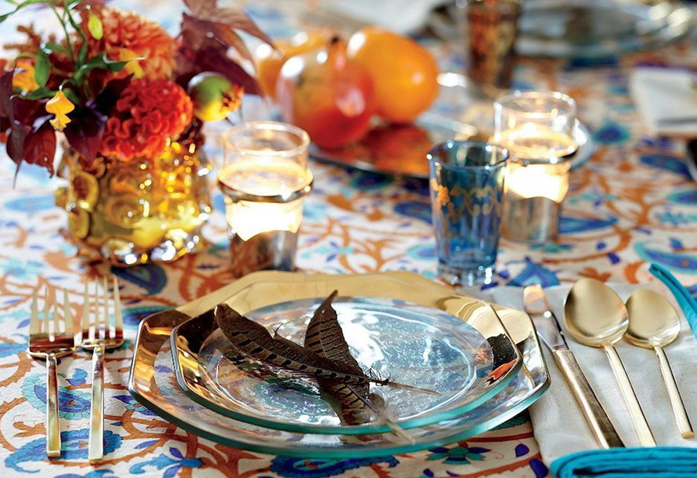 Silky feathers and blue glass blend create an exotic table setting