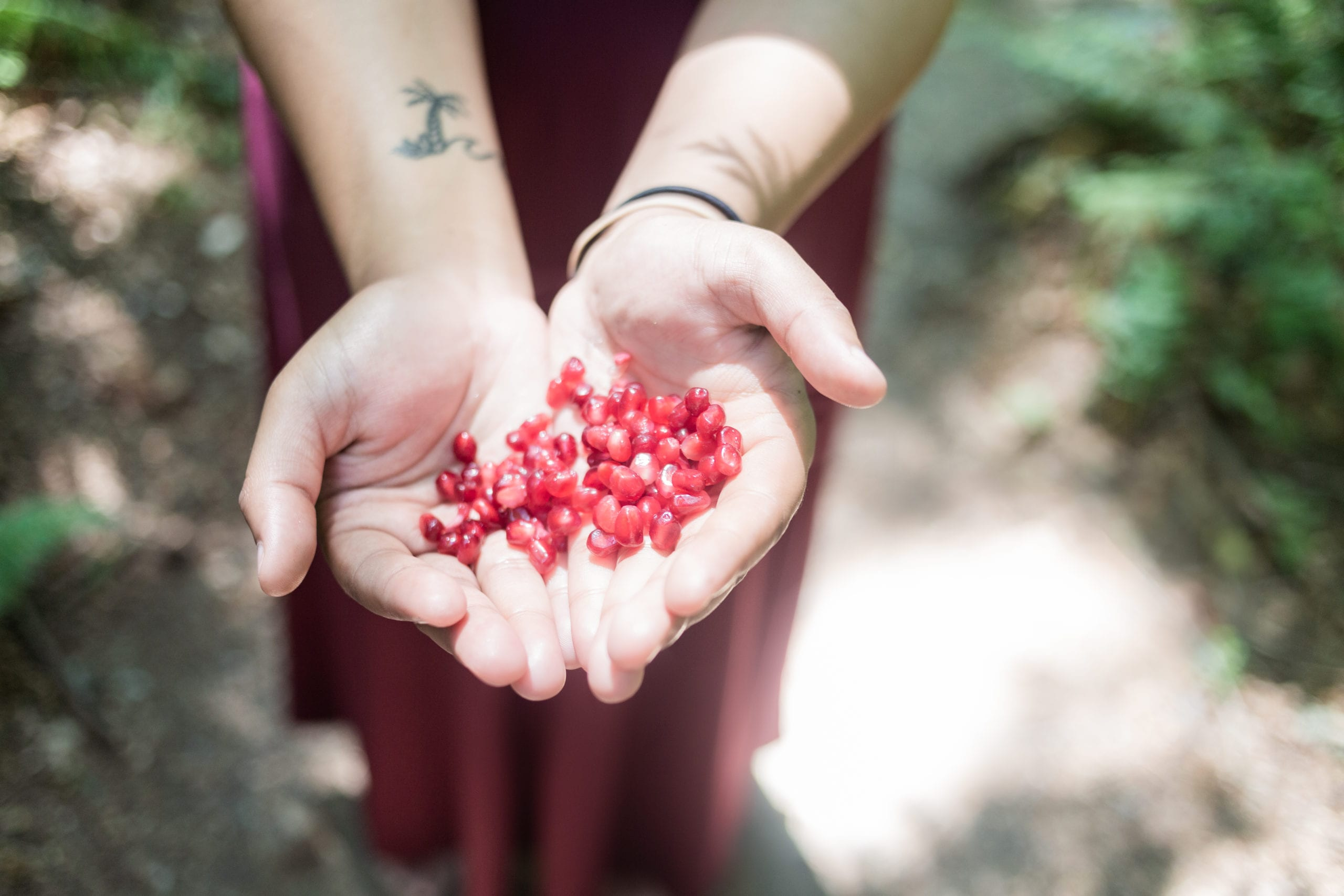 Persephone holding pomegranate seeds in her hands.