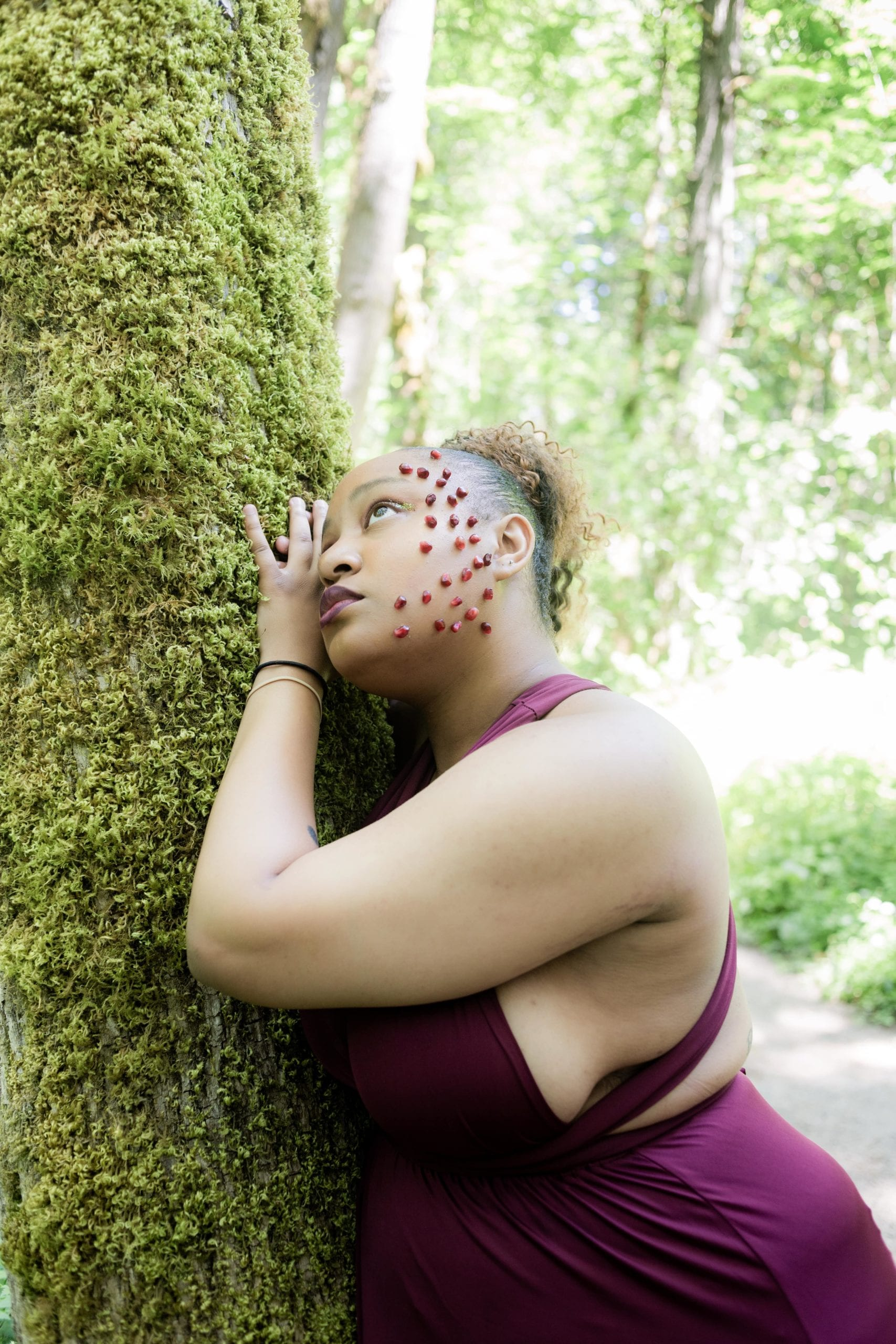 Reagan as Persephone leaning forward on a moss-covered tree with her head resting on her hands, looking up to the sky.