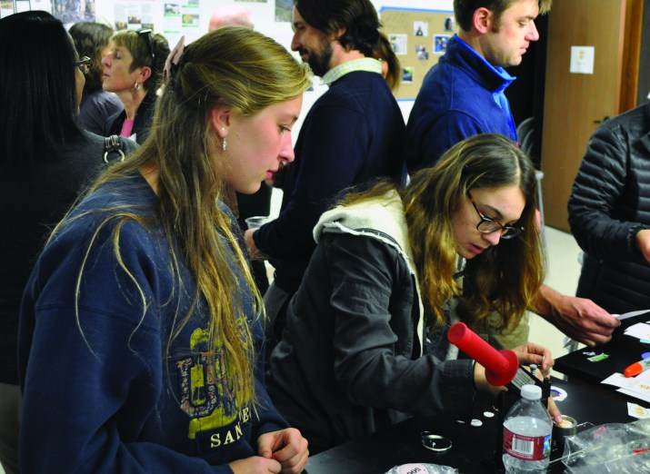 Two female students are in frame; the right has brown hair, wears glasses and is in the process of making a button at The Hive, while the other has long blonde hair and is looking at the button maker.