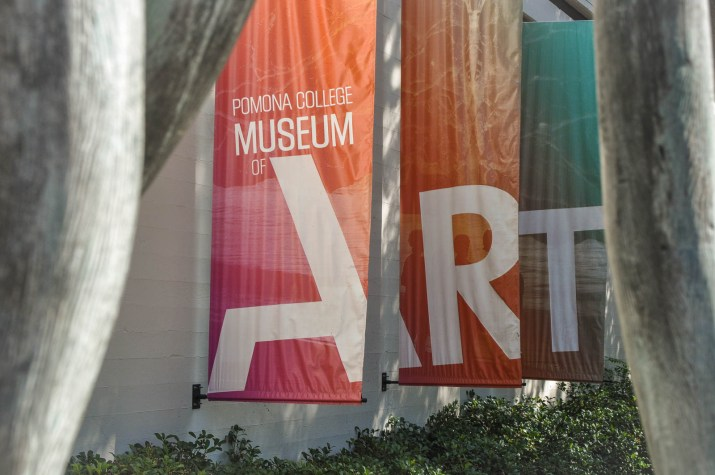 Three banners fly behind the former location of the Pomona Art Museum; they are red, orange and turquoise.