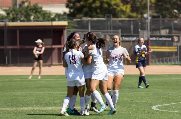 four girls in soccer uniforms hugging