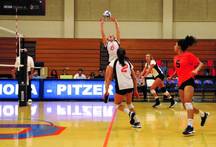 Woman jumping into the air to hit volleyball
