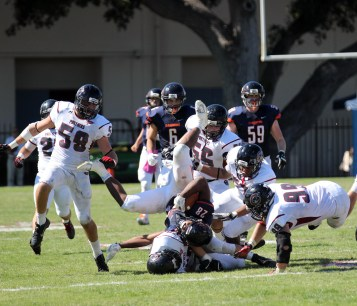 football players tackle each other