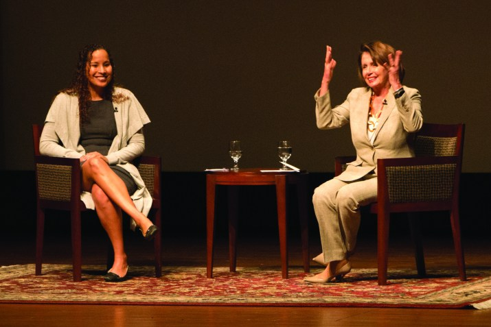 two women sit in chairs on a stage smiling