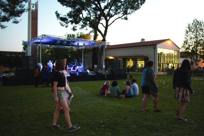 people gather in a grassy area with a building in the background
