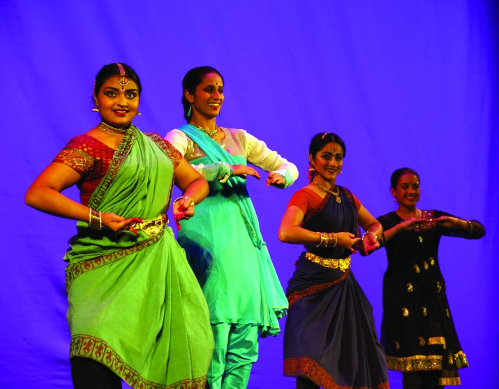 Four women in colorful garments dance on a stage