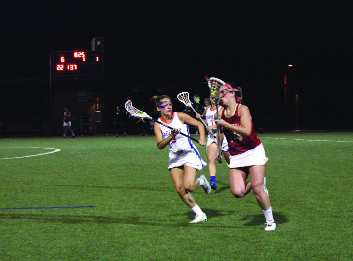 Two female lacrosse players running down a field