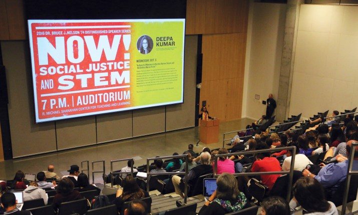 An auditorium filled with people and a screen displaying a message about social justice and STEM