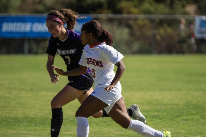 Two female soccer players race down a field
