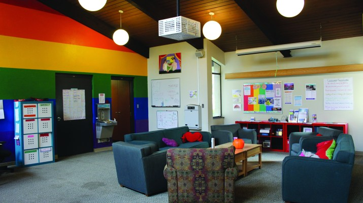 The inside of the Queer Resource Center. One wall is painted with rainbow stripes and there is a board of resources on wall. There are several chairs and couches around a central table.