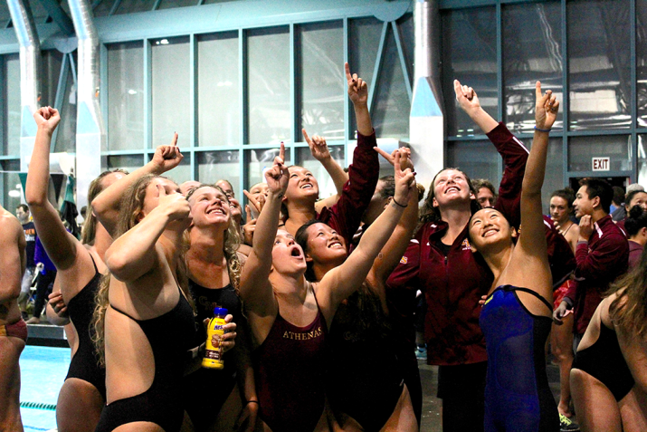 A group of female swimmers holds up the no. 1