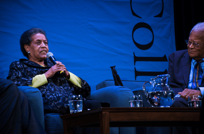 An older woman speaks into a microphone while sitting onstage