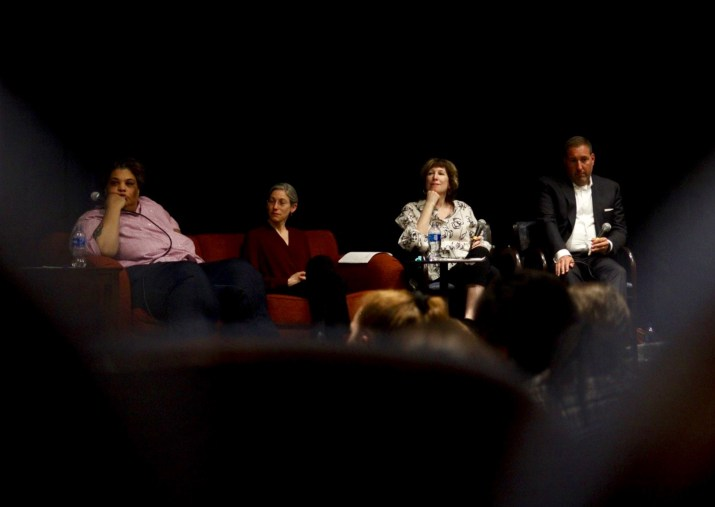 A panel of four speakers sits on a stage in the basement of a Pomona building