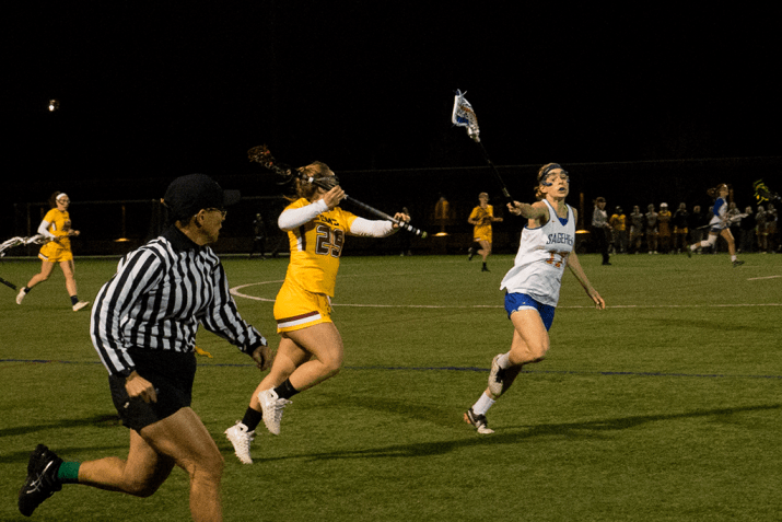 Juliana Clark SC '20 passes the ball to a teammate while Rebecca Long PO '17 attempts to block her. Clark wears a gold, white and maroon uniform while Long wears a white, blue and orange uniform.