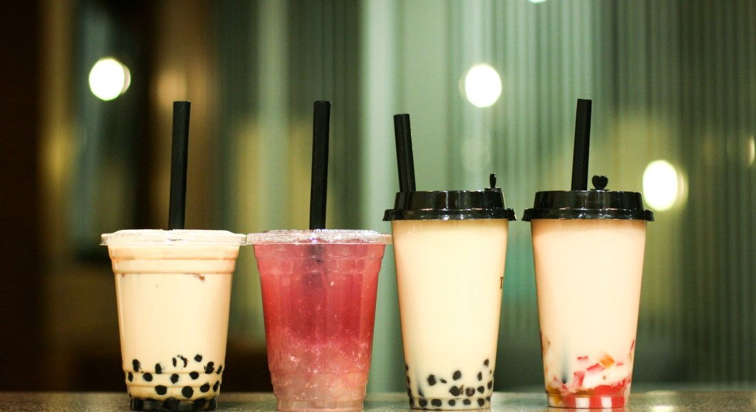 "Four bobas are lined up, from left to right: black milk tea with boba from Tocaja, ""Purple Me"" from Tocaja, black milk tea from T & Joy and rose milk tea from T & Joy."