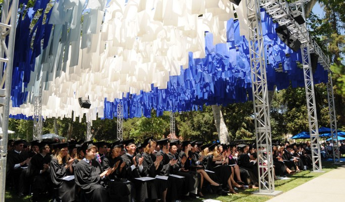 A group of students dressed in black graduation gowns sit under a canopy of white and blue streamers.