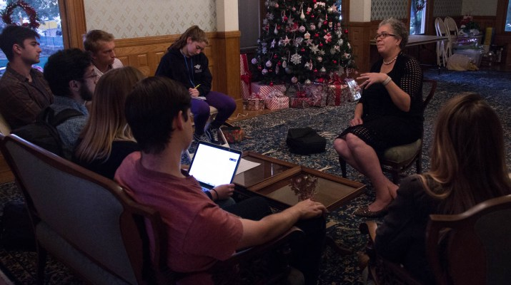 Pomona President G. Gabrielle Starr sits on a chair facing a group of students. She wears a black dress, black shoes, and glasses. Around her sit seven students, on a couch and several chairs.