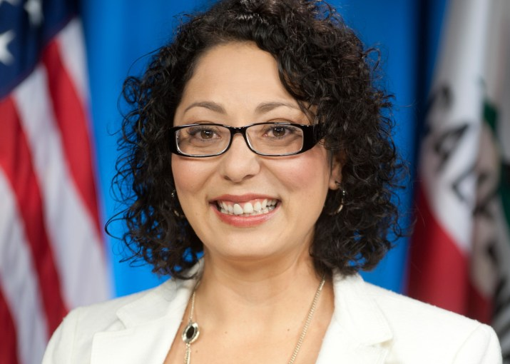 A photo of Cristina Garcia PO '99. She has curly dark brown hair, and she is wearing square glasses and a white blazer.