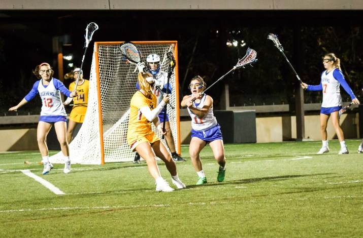 Emily Cohen CM '20, in yellow, looks for a shot as Sal Marx PO '18, in blue, rushes in to defend during the Pomona-Pitzer vs. Claremont-Mudd-Scripps lacrosse game Feb. 24.