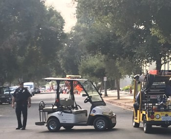 Campus Safety officer Clyde Phillips stands next to a golf cart on Bonita Avenue.