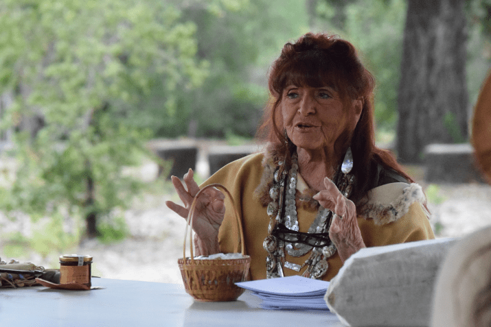 A woman with red hair and bangs sits at a table talking
