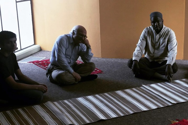Three Muslim men sit on the ground