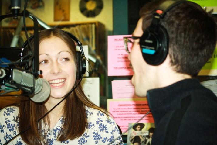 Two people with headphones on talk into microphones in radio studio