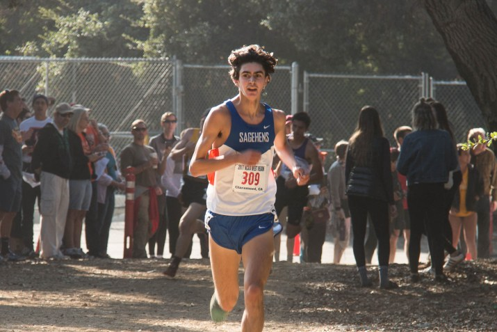 A male cross country runner sprints down a gravel path