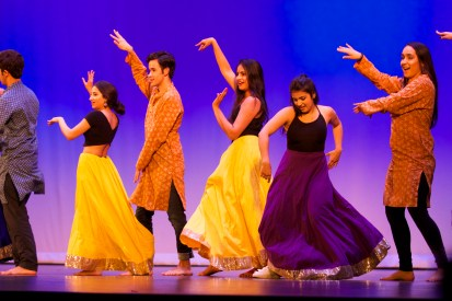 Students in colorful outfits dance onstage