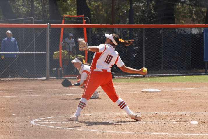 "Liz Rodarte PZ '19 throws a pitch. She is wearing a orange and white uniform with the number ""10."""