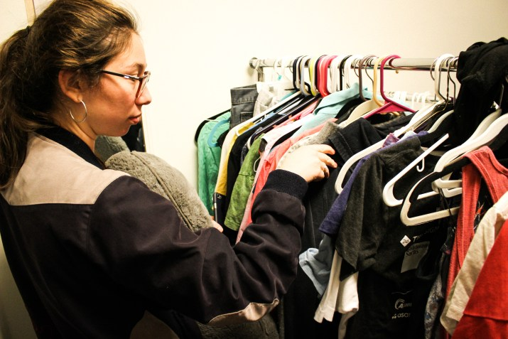 A woman looks through a rack of clothes