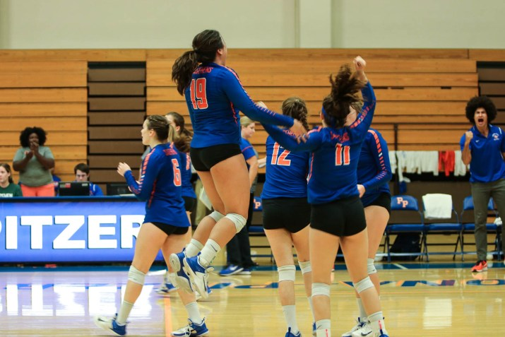 A group of female volleyball players jump up and down on the court