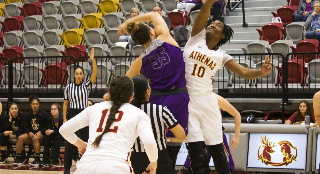 Maya Love CM '20 and Corinne Bogle CM '18 in the midst of a basketball tip-off. Both wear a white, maroon and gold uniform.