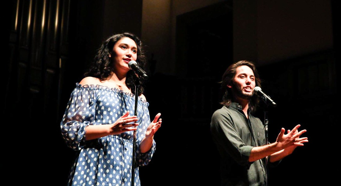 Slam poets Sarah Kay and Phil Kaye deliver a performance. Kay wears a blue and white polka dot dress while Kaye wears a green shirt.