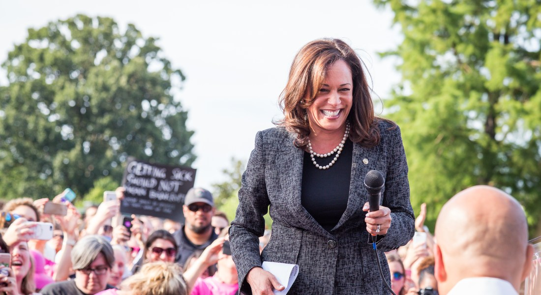 Kamala Harris, D-Calif., holding a microphone and smiling
