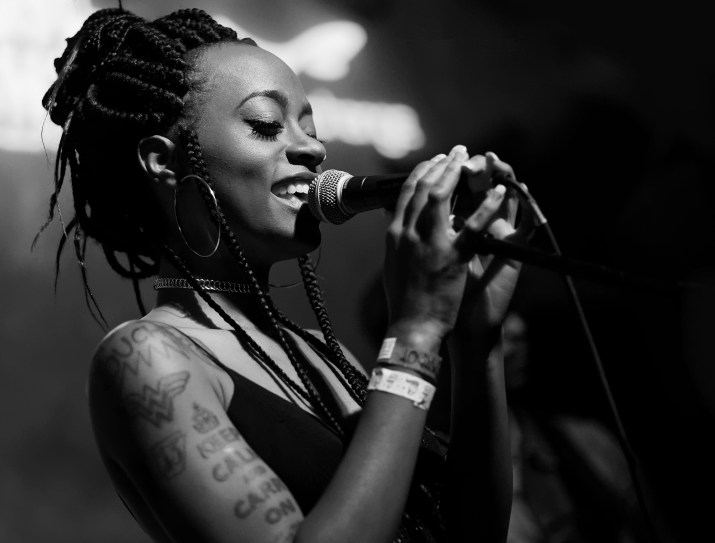 Kari Faux, a young African American woman, sings into a microphone while wearing a black tank top, hoop earrings, a necklace and bracelets.