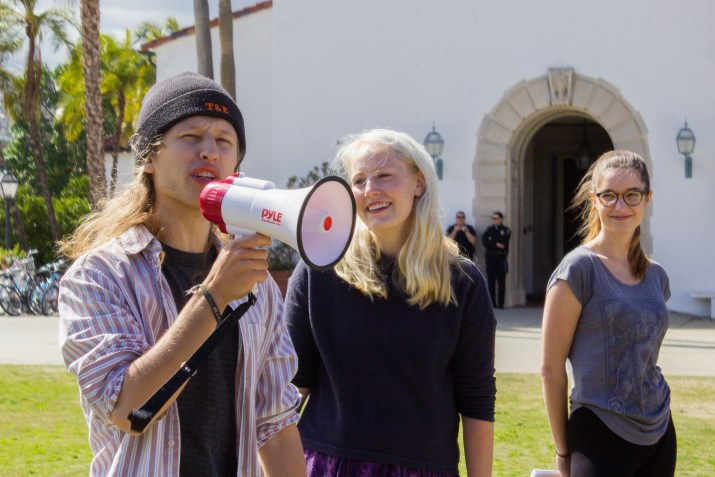 A male student speaks into a megaphone while two female students stand beside him.