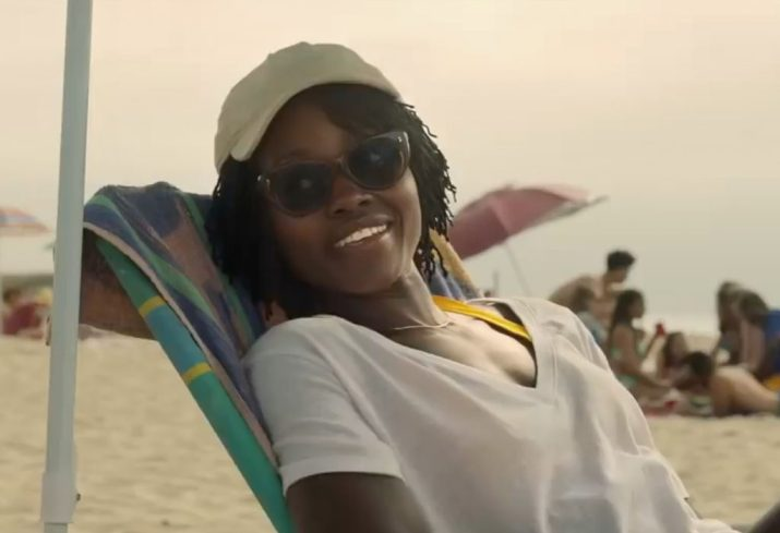 """Actress Lupita Nyong'o, who plays Adelaide in the new horror movie """"Us"""" sits on a beach chair in the shade wearing a white shirt, sunglasses and a white baseball cap."""