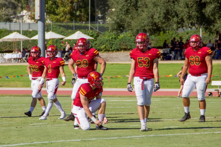 Six CMS football players, in red uniforms, walk off a field during a game against Chapman in 2018.